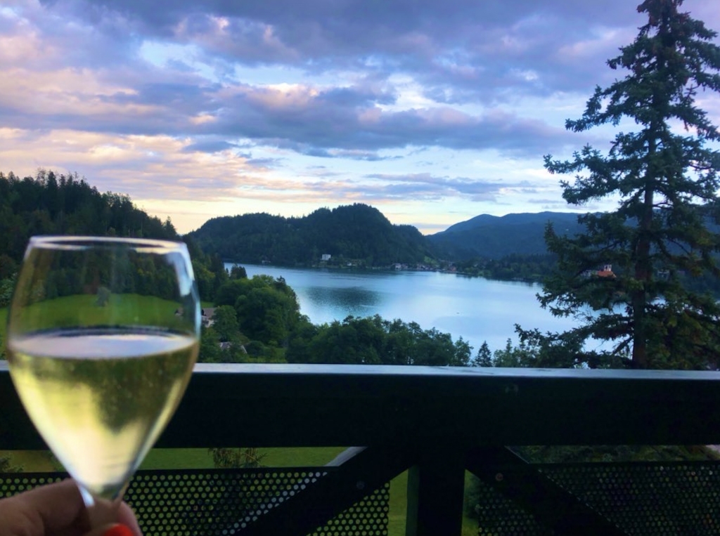 Glass of Champagne on balcony at Hotel Triglav at sunset overlooking Lake Bled