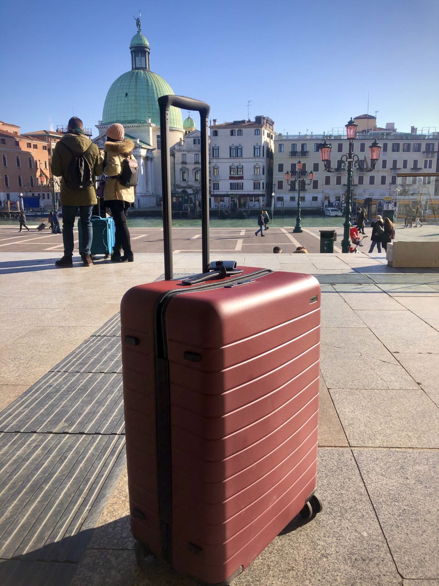 Suitcase in front of Venice train station with views of the Canal