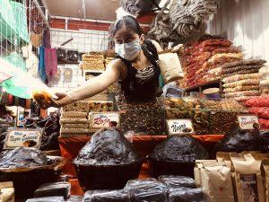 Woman offering a tasting of local produce at Mercado 20 de Noviembre, Oaxaca